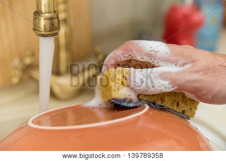 Man washes dish under stream of water in kitchen