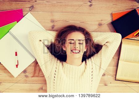 Young beautiful woman lying on the wooden with books.