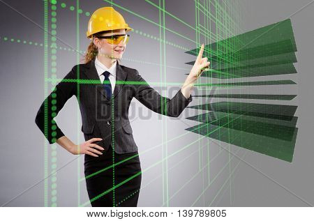 Female engineer with helmet pressing virtual button