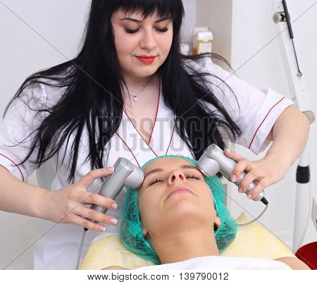 Young woman in hat receiving electric ultrasonic facial massage at beauty salon. Procedure vibro-cell electrotherapy.