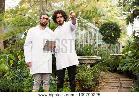 Male scientist pointing while coworker holding digital tablet outside greenhouse