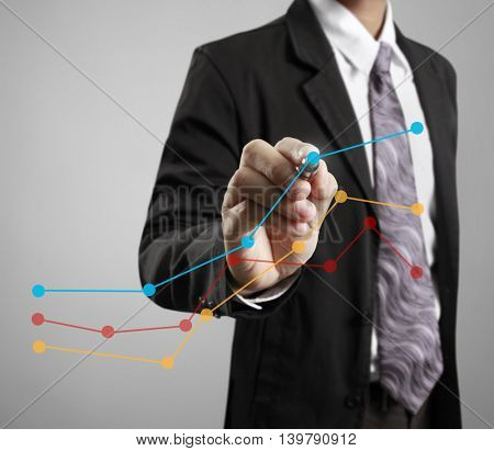 Businessman drawing graphics a growing graph