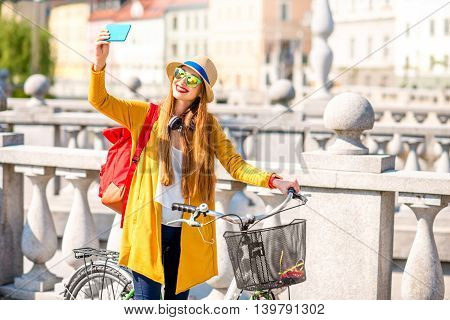 Young female traveler making self portrait with smart phone standing with bicycle on Triple bridge in Ljubljana. Traveling in Slovenia