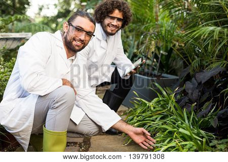 Portrait of happy male scientists inspecting plants at greenhouse