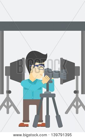 An asian young photographer working with camera on a tripod in photo studio. Man taking photo with professional digital camera in the studio. Vector flat design illustration. Vertical layout.