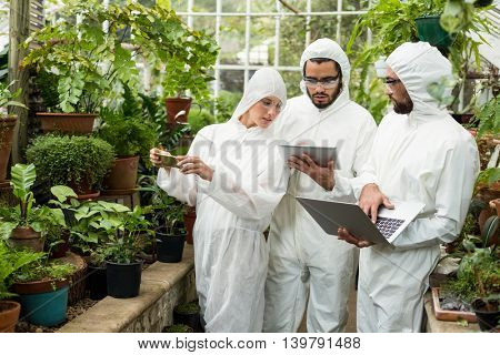 Scientists in clean suit discussing over technologies while examining plants at greenhouse