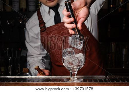 Bartender putting broken ice in a cocktail glass