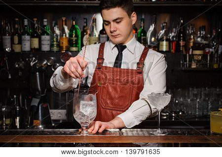 Bartender cooling cocktail glass with ice at the bar