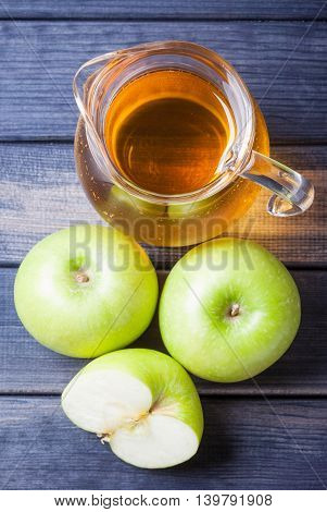 Apple juice in pitcher on table, vertical photo still life