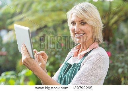 Portrait of happy mature female gardener using digital tablet at greenhouse
