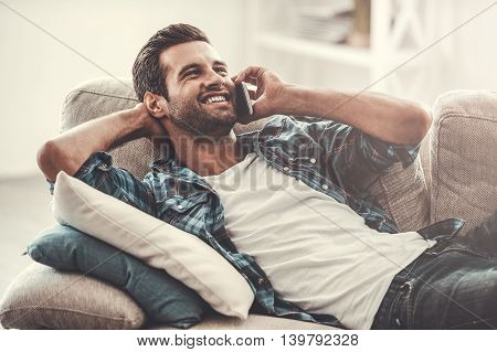 Leisure day at home. Joyful young man talking on the mobile phone and smiling while lying on sofa