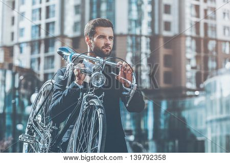 On his way to work. Confident young businessman carrying his bicycle on shoulder while crossing the road