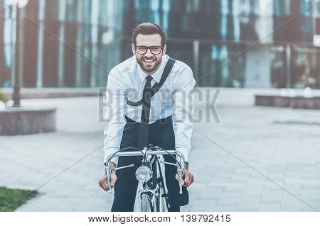 Eco way to get to work. Happy young businessman smiling and looking at camera while riding on his bicycle