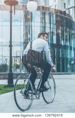 On the way to his office. Rear view of young businessman looking away while riding on his bicycle
