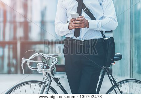 Typing business message. Close-up of young businessman holding mobile phone while leaning at his bicycle with office building in the background