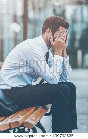 Feeling exhausted. Side view of frustrated young businessman covering his face by hands while sitting on the bench outdoors