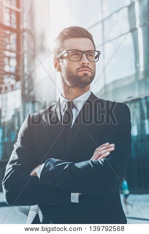 Young and successful. Low angle view of handsome young businessman keeping arms crossed and looking away while standing outdoors with office building in the background
