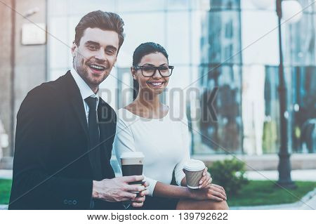 Enjoying coffee break together. Two happy young business people holding cups of coffee and looking at camera while sitting outdoors