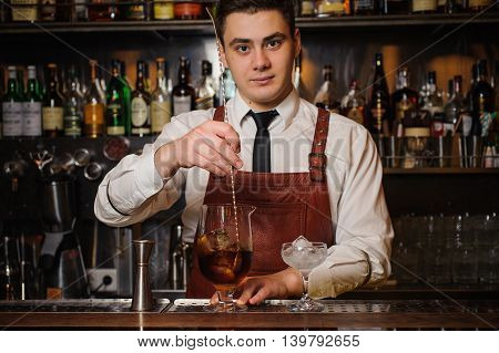 Bartender is stirring cocktails on the bar counter. na face