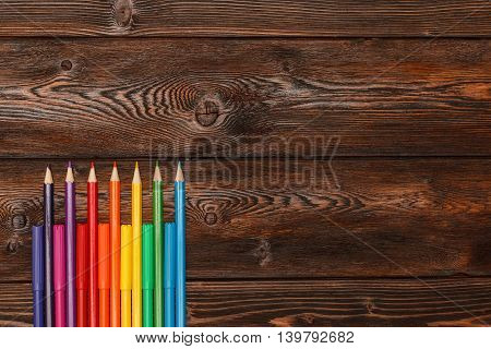 Lots of assorted colors marker pens and pencils with copyspace on dark wooden background