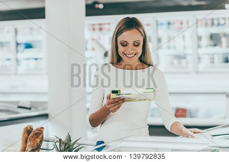 Checking the ingredients. Cheerful young woman holding food from refrigerator while standing in a food store