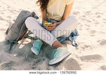 Young slim girl sitting on the beach in jeans and a yellow T-shirt and listening to music with headphones and mobile phone