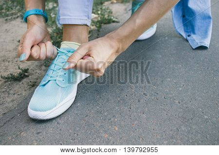 Close-up of girl ties the laces on the shoes while walking around the city