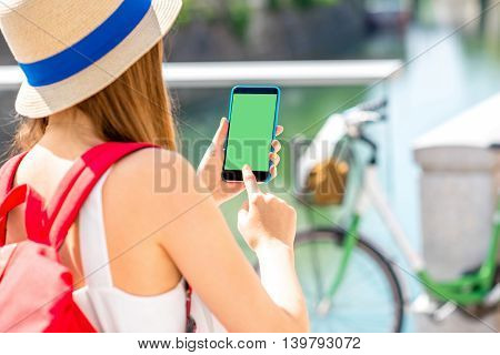 Female traveler holding smart phone with green screen on the street with bicycle on the background.