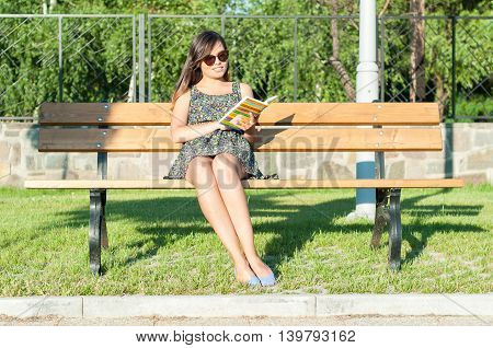 Pretty Lady Sitting On Bench And Reading