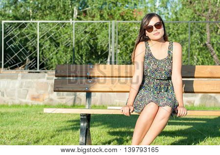 Beautiful Girl Sitting On Bench Outside In Park