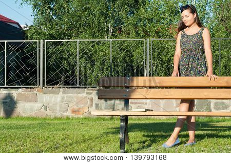 Beautiful Young Lady Posing In Park Standing Beside Bench