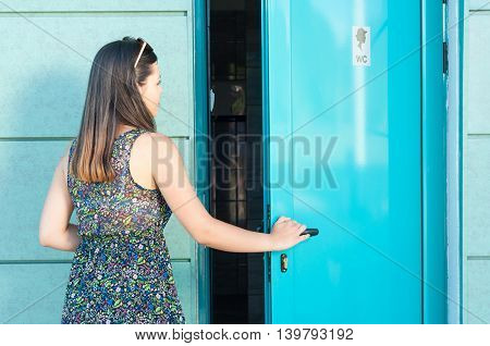 Young Woman Entering Public Toilet Outside In Park