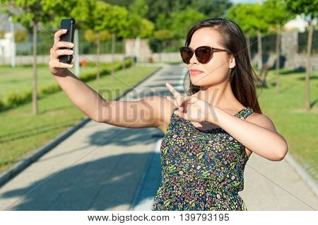 Girl Taking Selfie And Showing Peace Sign