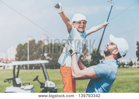 My little winner! Excited young man picking up his son while standing on the golf course