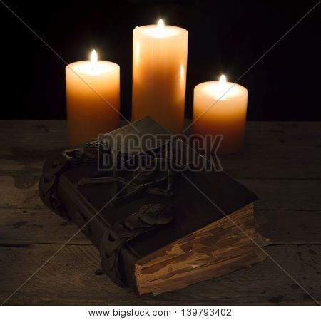 Closed black magic book with three candles in the darkness