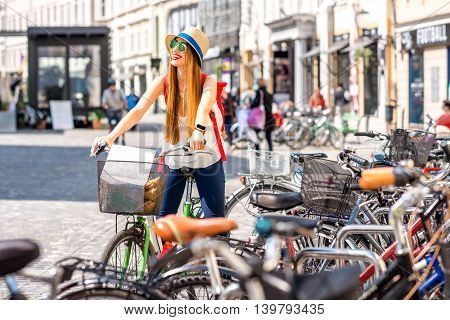 Young female tourist sitting on the bicycle on the street near bicycle parking in the old city center of Ljubljana. Traveling in Slovenia