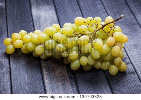 bunch of grapes on wooden table photo still life
