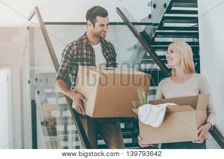 Moving to a new home. Happy young couple holding cardboard boxes while going down the stairs