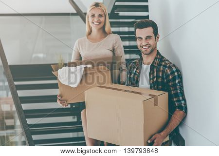 Just moved in. Cheerful young couple holding cardboard boxes while standing on the stairs of their new house