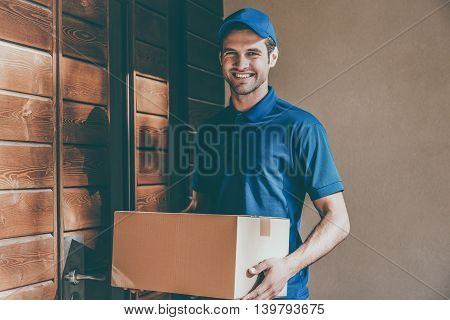 Happy delivery man. Happy young courier holding a cardboard box while standing against door of residential house