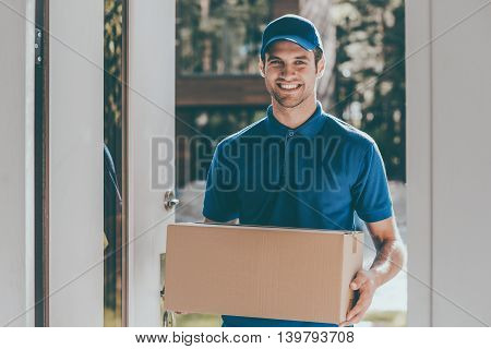 Confident delivery man. Cheerful young courier holding a cardboard box while standing at the entrance of apartment