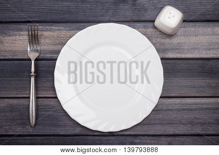 empty plate fork and salt shaker on wooden table