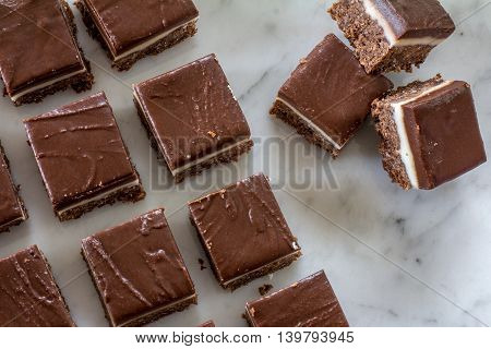 Chocolate Peppermint Slice Cut Up on Marble Cutting Board from Above