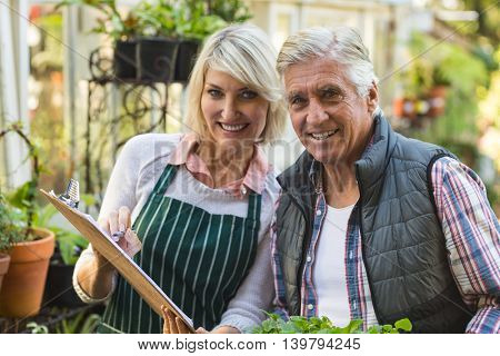 Portrait of confident male and female gardeners outside greenhouse