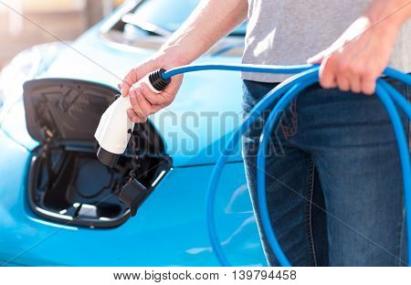 It is so easy in use. Close up of hands of a man twisting up a power connector for an electric vehicle with an electric car on the background