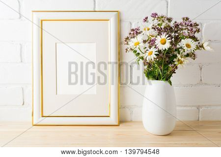 Frame mockup with wild flowers bouquet. Portrait or poster white frame mockup. Empty white frame mockup for presentation artwork.