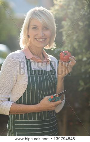 Portrait of happy female gardener showing fresh tomato while standing by trees