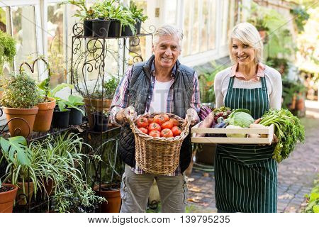 Portrait of happy gardeners carrying fresh vegetables outside greenhouse