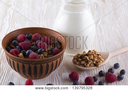 Muesli with fresh berries and milk on wooden background.