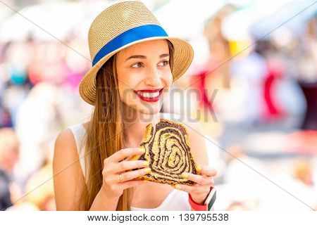 Young woman tasting traditional slovenian dessert Potica at the open market square in Ljubljana. Slovenian street food. Close up view with small depth of field.